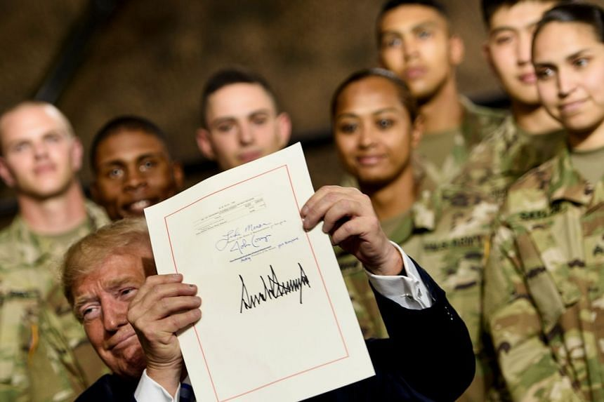 US President Donald Trump holding the US$716 billion (S$985 billion) defense policy Bill after signing it at Fort Drum, New York, on Aug 13.