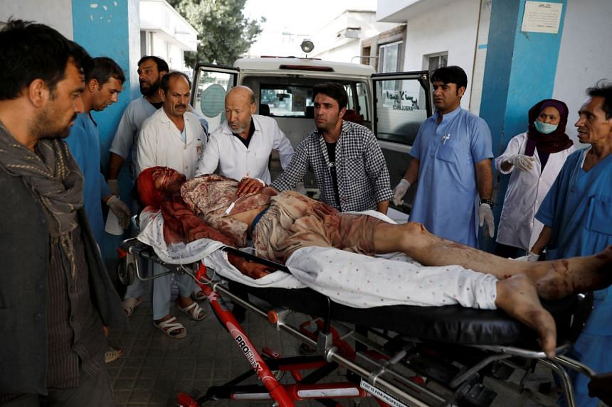 An injured man is carried to hospital after a blast in Kabul, Aug 15, 2018.
