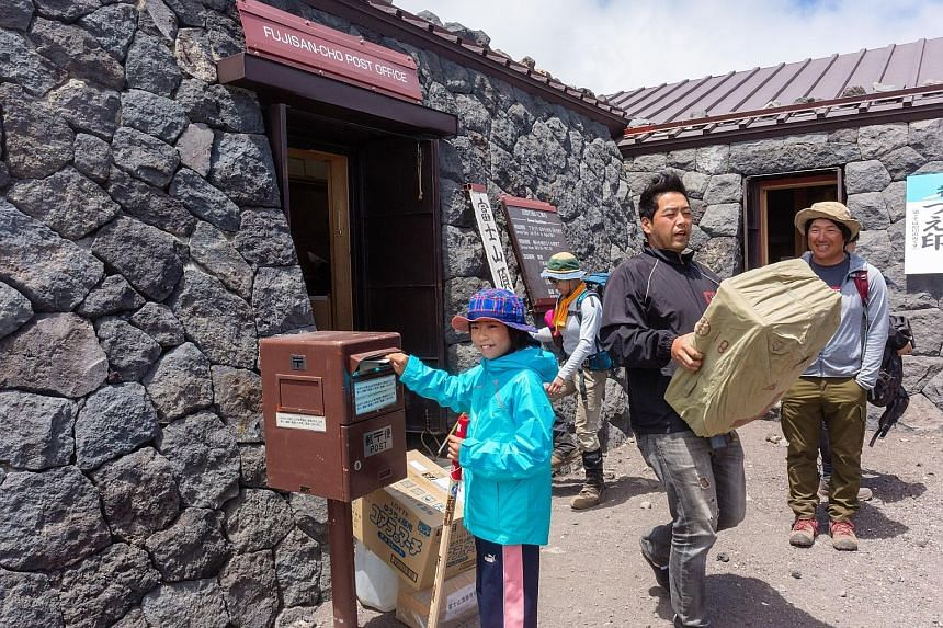 A young hiker uses a mailbox outside the post office on the summit of Mount Fuji in Fujinomiya, Japan.