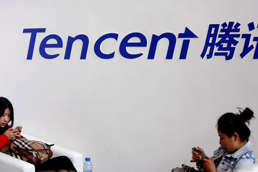 Visitors use their smartphones underneath the logo of Tencent at the Global Mobile Internet Conference in Beijing, on May 6, 2014.