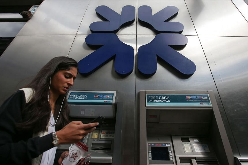 A woman looks at her smartphone as she passes ATMs outside an RBS branch in London.