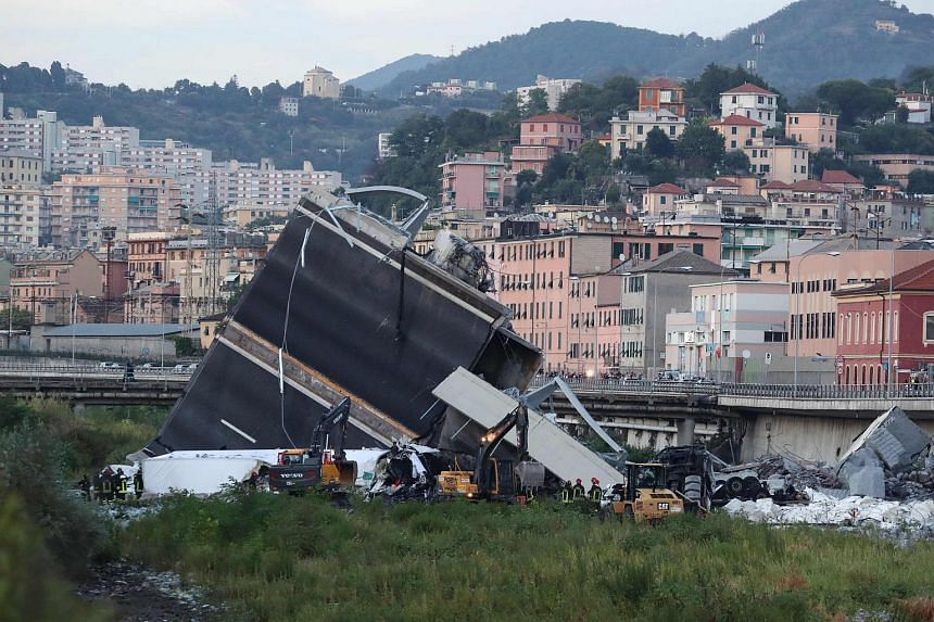 Rescuers inspect the rubble and wreckage by the Morandi motorway bridge after a section collapsed in Genoa, on Aug 14, 2018.