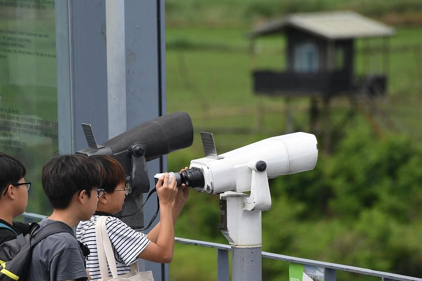 Visitors look through binoculars at a viewing deck of Imjingak peace park near the Demilitarised Zone dividing South Korea and North Korea in Paju, on June 11, 2018.