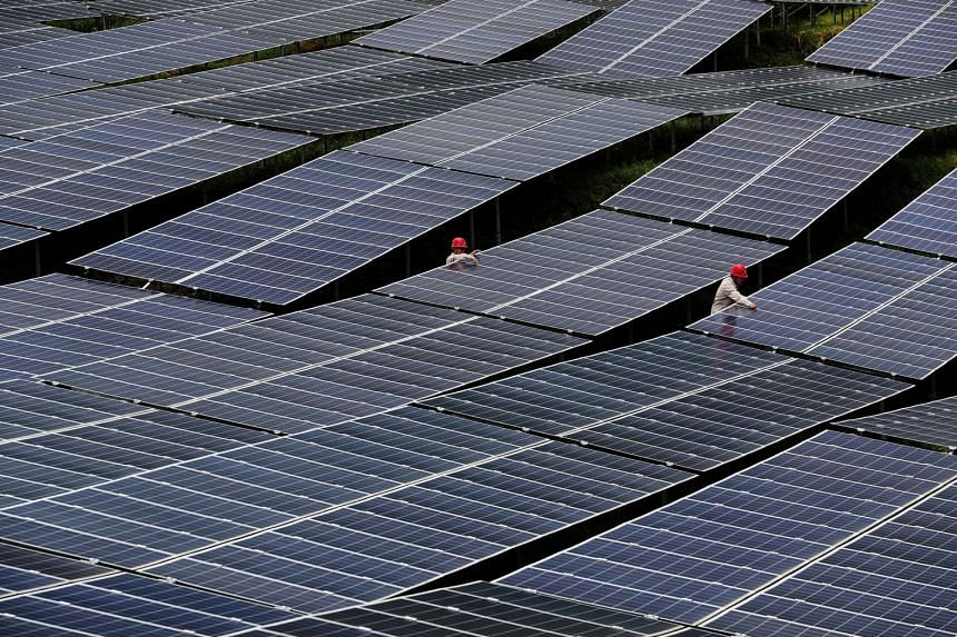 Workers checking solar panels at a photovoltaic power station in Chongqing, China.
