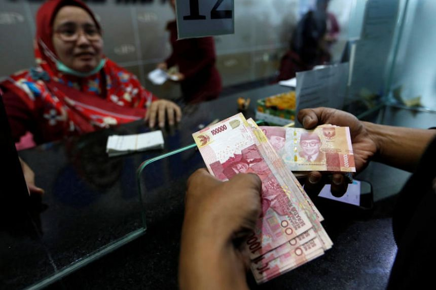 A customer holds Indonesian rupiah bank notes at a money changer in Jakarta.