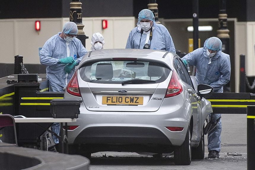 Forensics officers examining the vehicle that crashed outside the Houses of Parliament in London on Tuesday. Police believe a car was deliberately driven into pedestrians and cyclists, injuring three people, before ramming a security barrier outside