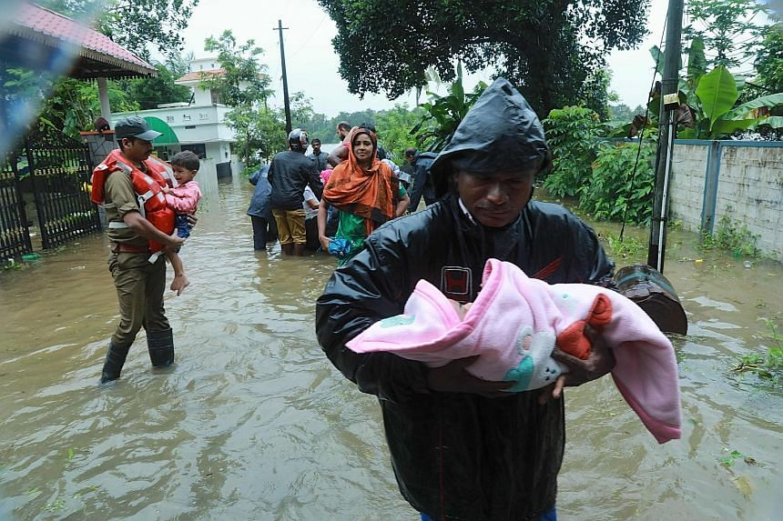 Rescue personnel using an inflatable boat to evacuate stranded residents in Kerala yesterday.