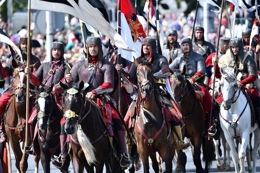 People in historical costumes taking part in the Grand Polish Armed Forces Parade, marking Polish Armed Forces Day in Warsaw, Poland, yesterday. Reports state that 100 aircraft, including helicopters, 1,000 soldiers and re-enactors in historical cost