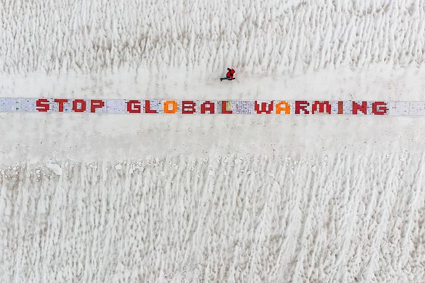 A jogger running next to a giant roll of more than 2,500 laminated postcards displayed for an exhibit calling for action against climate change in the Swiss Alps on Monday. Scientists say that global warming from climate change will not be the only c