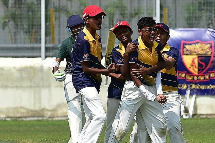 Anglo-Chinese School (Independent) bowler Pranav Nitin Maheshwari (being hugged), 13, celebrates after running out a Raffles Institution batsman during the Schools National C Division cricket final yesterday at the Ceylon Sports Club. ACS (I) beat ar