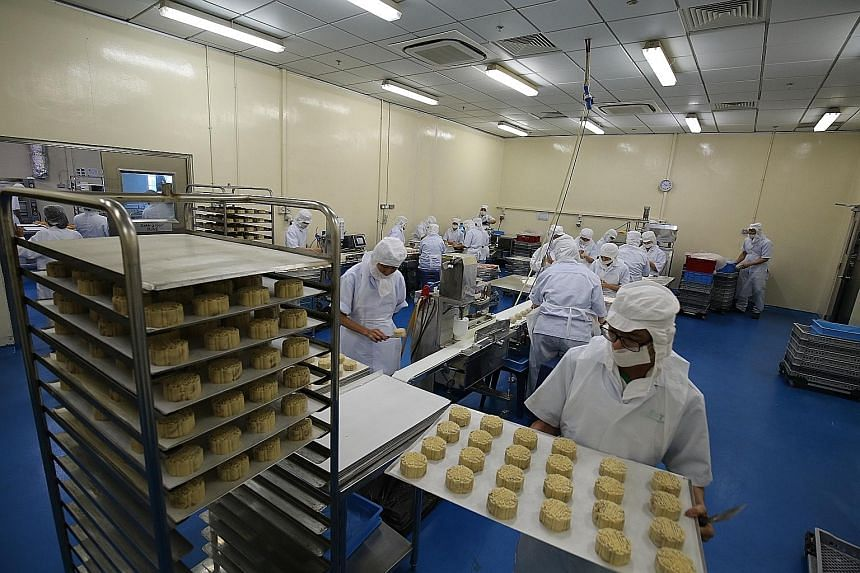 Workers at TungLok's production facility in Sembawang. About 80 per cent of the mooncakes sold at its restaurants are now lower in sugar.