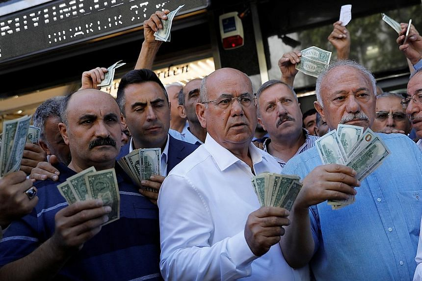 Businessmen holding US dollars in front of a currency exchange office in Ankara on Tuesday, after Turkish President Recep Tayyip Erdogan called on Turkish citizens to sell their dollar and euro savings to support the lira.