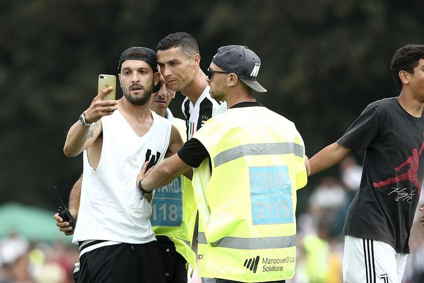 Juventus supporters invaded the pitch to take a picture with Cristiano Ronaldo at the end of the first half of the friendly football match between Juventus A and Juventus B at Villar Perosa, on Aug 12, 2018.