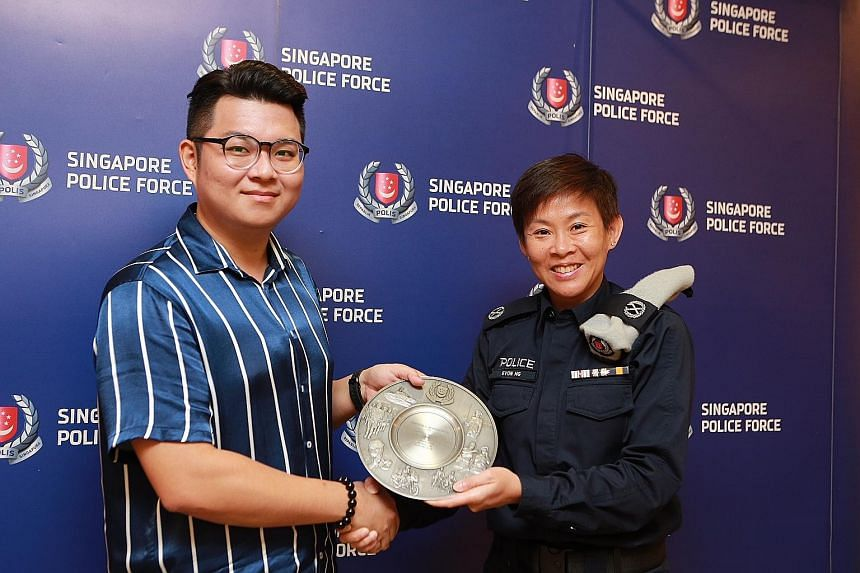 Engineer Goh Tong En receiving his award from Deputy Assistant Commissioner of Police Evon Ng yesterday. He was commended for preventing a man from taking upskirt videos on an escalator at Marsiling MRT station last month.