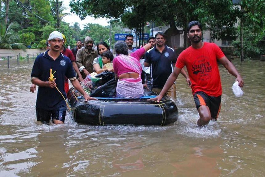 Indian volunteers and rescue personnel evacuate local residents in a boat in a residential area at Kozhikode, Kerala, on Aug 16, 2018.