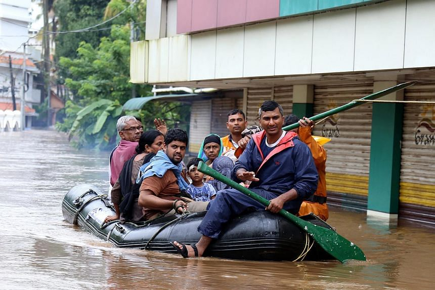 Residents use an inflatable boat to reach a safer place during the flood in Kochi, Kerala, on Aug 16, 2018.