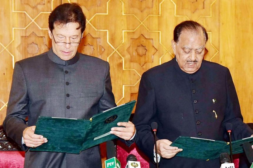 Imran Khan (left) is sworn in as prime minister by Pakistan President Mamnoon Hussain.