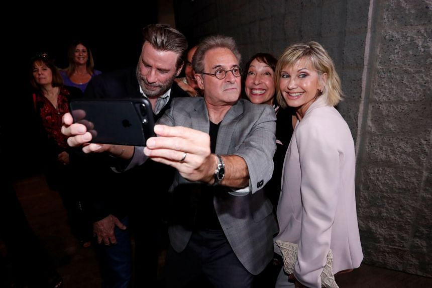 From left: Cast members John Travolta, Barry Pearl, Didi Conn and Olivia Newton-John pretend to look away as they pose for a selfie at a 40th anniversary screening of Grease at the Academy of Motion Picture Arts and Sciences in Beverly Hills, on Aug