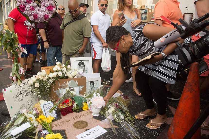 A fan signing a board covering one of the windows at the house in Memphis where Franklin was born. Flowers and mementoes left at Aretha Franklin's star on the Hollywood Walk of Fame in Los Angeles on Thursday. The marquee on Fox Theatre in memory of