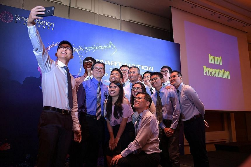 Minister-in-Charge of the Smart Nation Initiative Vivian Balakrishnan (centre), Cyber Security Agency of Singapore deputy chief executive (development) Teo Chin Hock (third from left), GovTech CEO Kok Ping Soon (kneeling) and IMDA CEO Tan Kiat How (f