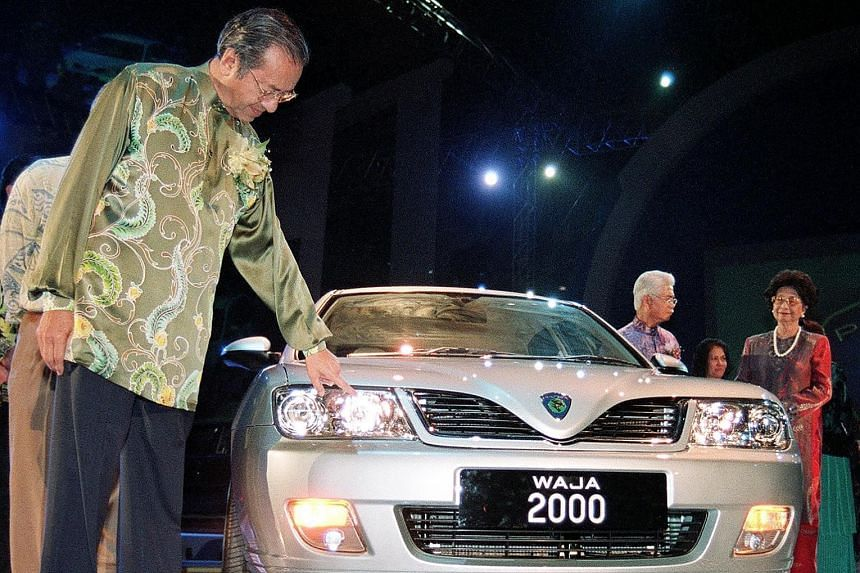 Dr Mahathir inspecting a newly launched Proton Waja in Shah Alam, Malaysia, in 2000. Dr Mahathir receiving a Japanese national football jersey from his Japanese counterpart, Mr Shinzo Abe, in Tokyo in June. Dr Mahathir wants to increase Malaysia's pr