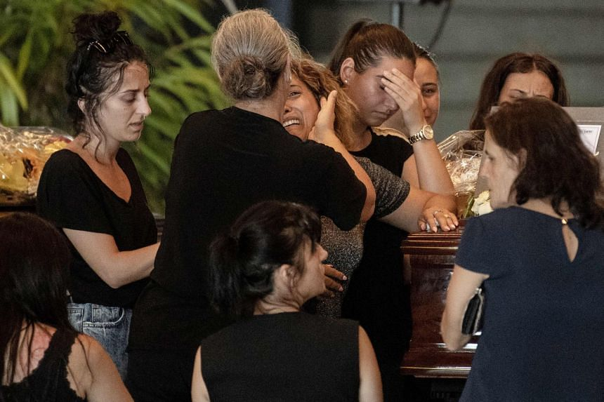 Relatives pray and pay their respects near the coffin of a victim of the Morandi bridge collapse.