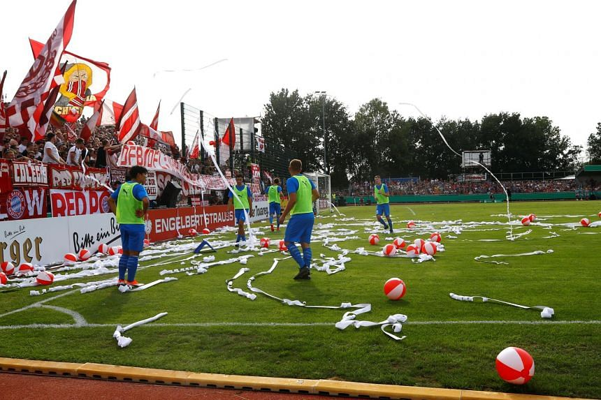 Drochtersen/Assel players clear objects thrown onto the pitch by fans.