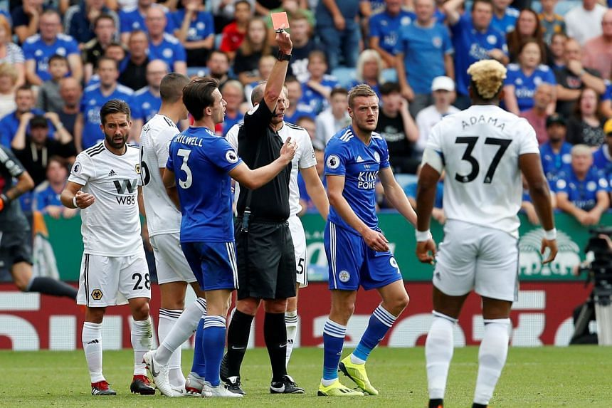 Leicester City's Jamie Vardy is shown a red card by the referee.