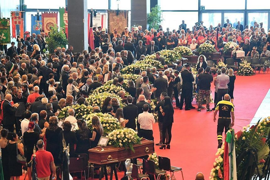 People at the state funeral applauding as members of the fire brigade, rescue teams and police arrived at the exhibition centre in Genoa yesterday. The mass was held for 19 of those killed in the bridge collapse, but some families boycotted the event
