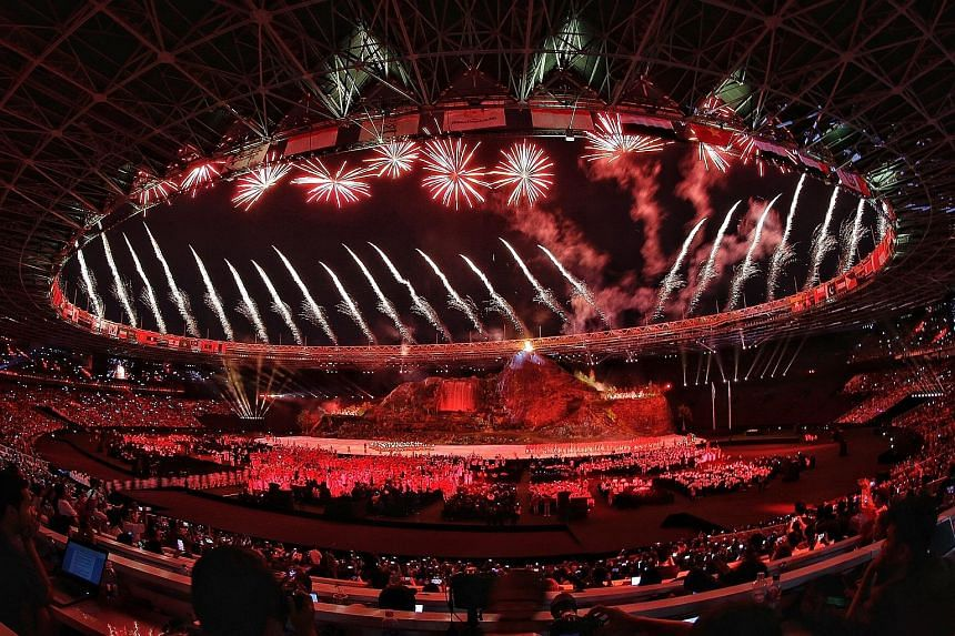 Above: Gymnast and flagbearer Hoe Wah Toon leading the Singapore delegation at the opening ceremony of the 2018 Asian Games in Jakarta. Below: At Jakarta's Gelora Bung Karno Main Stadium, 40,000 spectators were entertained by pyrotechnics and cultura