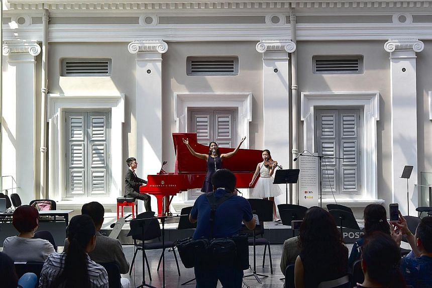 Performing imagin.Asia, an original composition, to an appreciative audience at the National Museum of Singapore yesterday were (from far left) Isaiah Hui, 13, who composed the song, Ms Ananya Diddapur, 18, and Lavinia Tsai, 14. The trio were partici