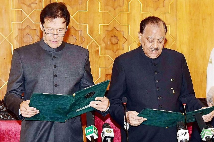 Pakistan's new Prime Minister Imran Khan, with President Mamnoon Hussain (far right) beside him, reciting the oath of office in Islamabad yesterday.