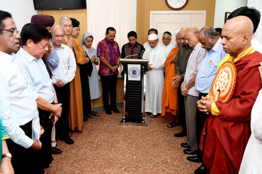 Senior Minister of State for Defence and Foreign Affairs Mohamad Maliki Osman (centre) and representatives of various religious communities holding a silent prayer session for those affected by recent earthquakes in Lombok, Indonesia, at the Inter-Re