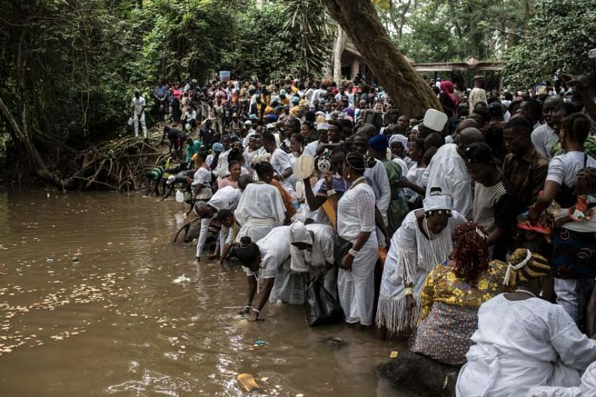 Devotees and participants offer sacrifices and prayers to the Osun river goddess and collect water from the sacred river during the Osun-Osugbo Festival in Osogbo, southwestern Nigeria, on Aug 17, 2018.