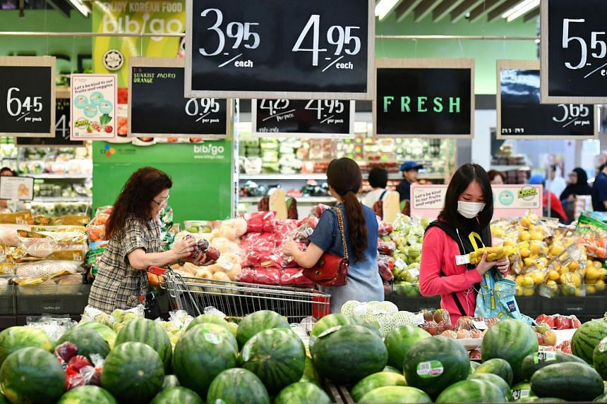 Customers at the fruits section at FairPrice Xtra supermarket in NEX on March 23, 2017.