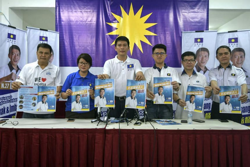 Malaysian Chinese Association's candidate for the Balakong state-seat by-election Tan Chee Teong (third from left) and other party activists showing the party's election manifesto.