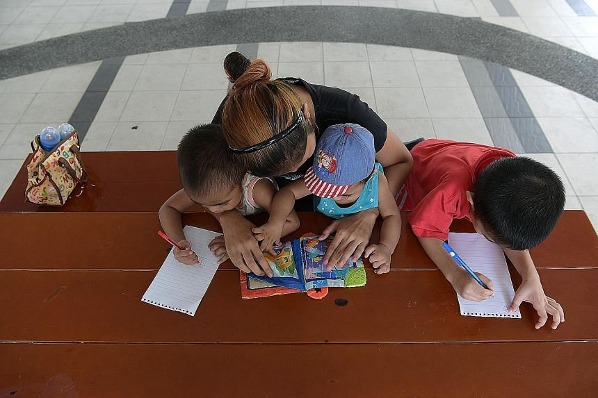 Housewife Shaodah Roslan, 28, with three of her seven children. Her husband works odd jobs and brings home up to $700 a month.