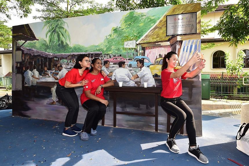 Yishun Community Hospital nurses (from left) Nur Rafiqah, 21, Saroja Muniandy, 55, and Wendy Yew, 22, who also took part in a litter-picking exercise, posing for a wefie at the newly launched mural which depicts what the area looked like in the 1960s