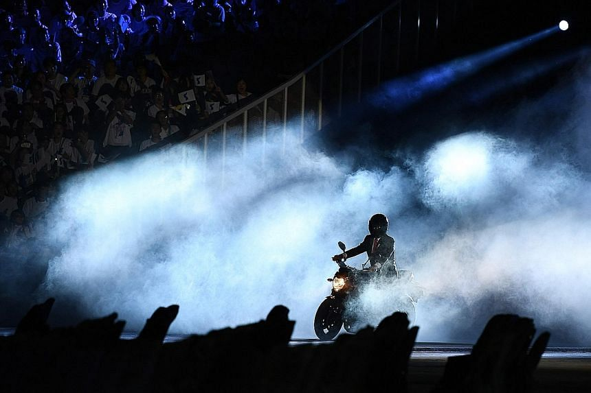 A man purporting to be Indonesian President Joko Widodo riding a motorcycle during the opening ceremony of the 2018 Asian Games at the Gelora Bung Karno stadium in Jakarta on Saturday. The video of Mr Joko, a self-confessed motorcycle fan, hopping on