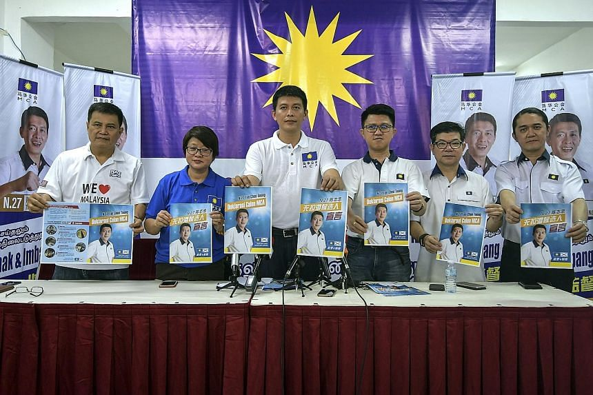 "Pakatan Harapan candidate Wong Siew Ki in front of a version of the PH logo, which has an arrowhead replacing the letter ""A"" in the middle of the word ""Harapan"". Malaysian Chinese Association candidate Tan Chee Teong (third from left) and other party"
