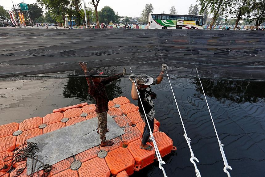 Workers on a makeshift raft installing nets last month to cover a polluted river beside the Athletes' Village at Kemayoran district in Jakarta. The country has spared no effort to ensure a successful Games.