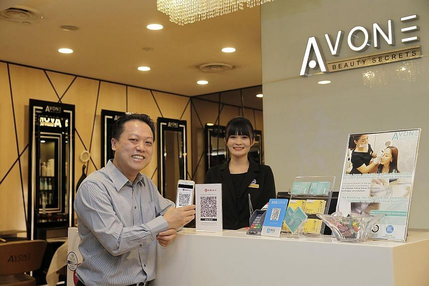 Mr Gavin Teo, managing director of beauty salon chain Avone Beauty Secrets, with branch manager Sammi Zheng. Mobile payment is a worldwide trend and if companies do not adapt, they will be left behind, says Mr Teo.