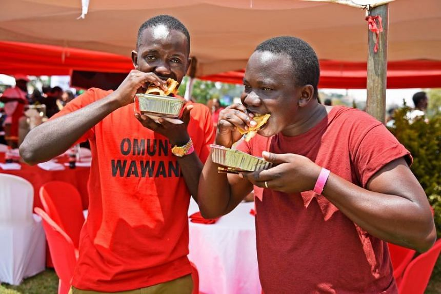 Men eat a Rolex during the Kampala Rolex festival in Kampala, on Aug 19, 2018.