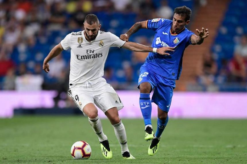 Getafe's Uruguayan defender Damian Suarez challenges Real Madrid's French forward Karim Benzema (left) during the Spanish League football match between Real Madrid and Getafe at the Santiago Bernabeu stadium in Madrid on Aug 19, 2018.