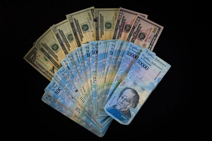 Venezuelan bolivar banknotes and US dollar bills in Caracas, where new banknotes will be issued on Aug 20, 2018.