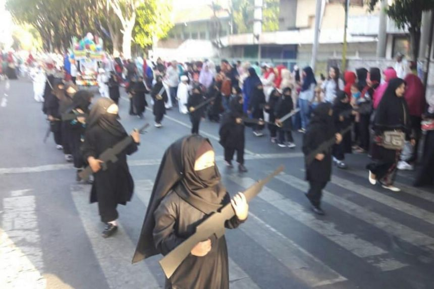 Children marching in black robes and carried props resembling assault rifles in a parade on Aug 17. This generated comments accusing the kindergarten of fomenting radicalism in a country that has long struggled with militant attacks.