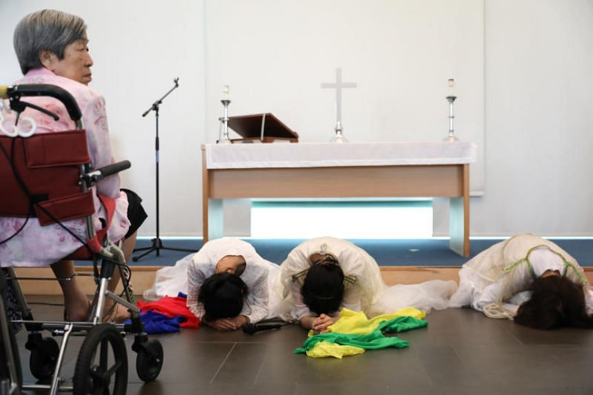 Japanese Christian activists kneel and bow down as Mdm Kuan Geok Poh (left, in pink), 81, looks on.