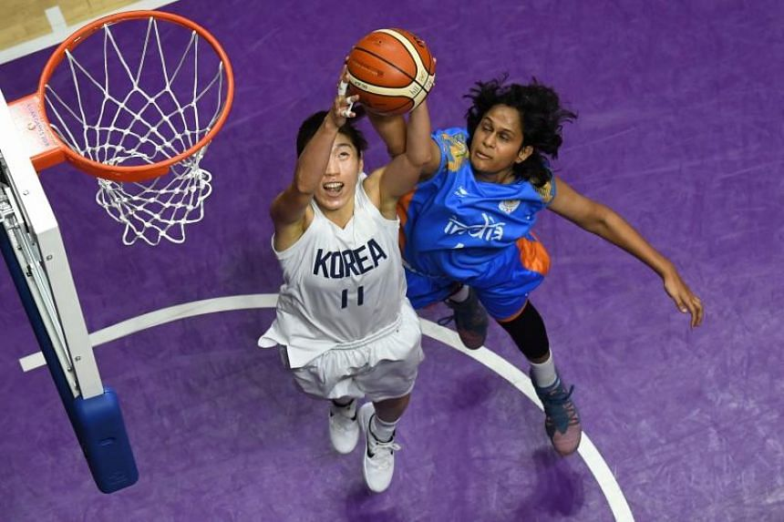 Unified Korea's Lim Yung-hui (left) goes for the basket against India's Shireen Limaye in the women's basketball preliminary match between Unified Korea and India during the 2018 Asian Games in Jakarta, on Aug 20, 2018.
