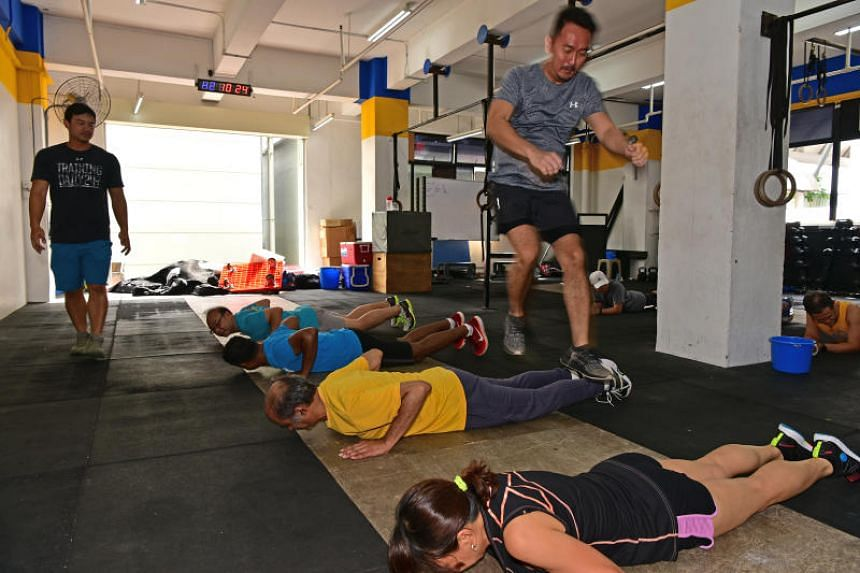 Participant jumping over others as part of cross fit training for ST Run.