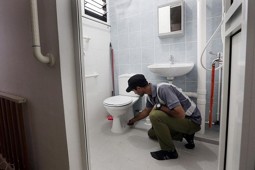 Above: A supervisor inspecting a toilet with elder-friendly features installed under the Enhancement for Active Seniors programme, which is part of the Home Improvement Programme (HIP). Left: A supervisor inspecting the gate of a Jurong flat under th